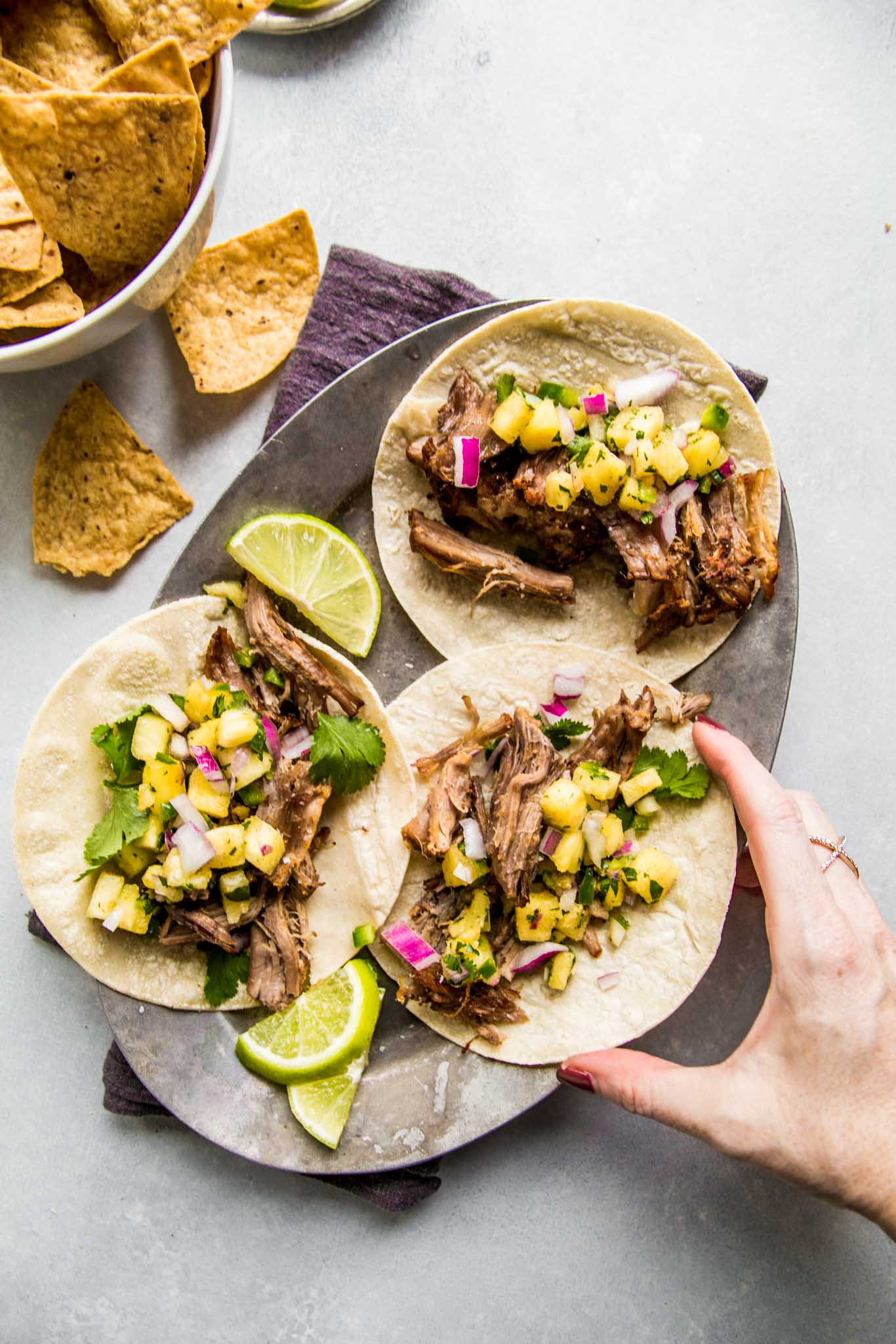 Hand reaching for carnitas street tacos.