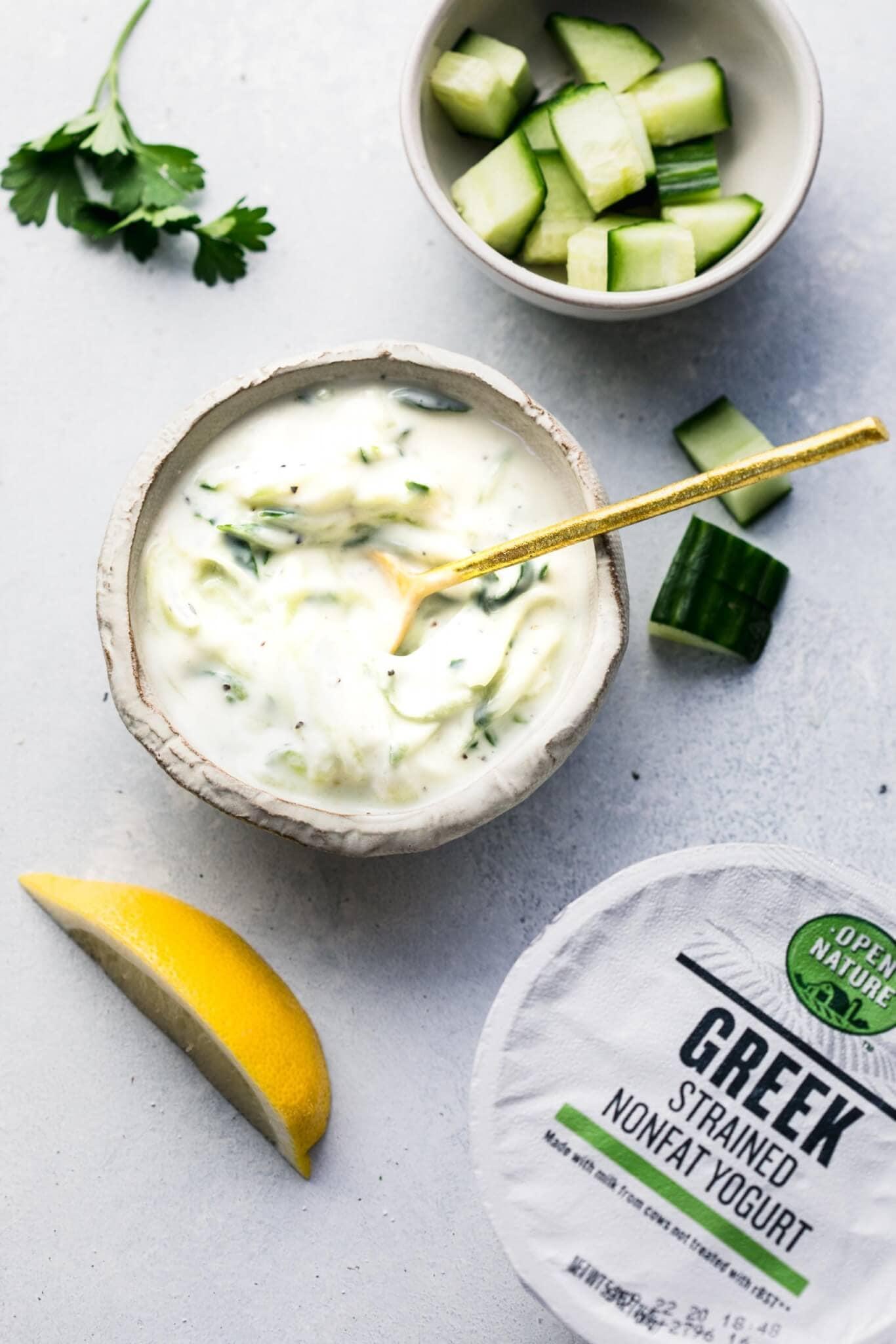 Container of greek yogurt next to small bowl of prepared tzatziki sauce