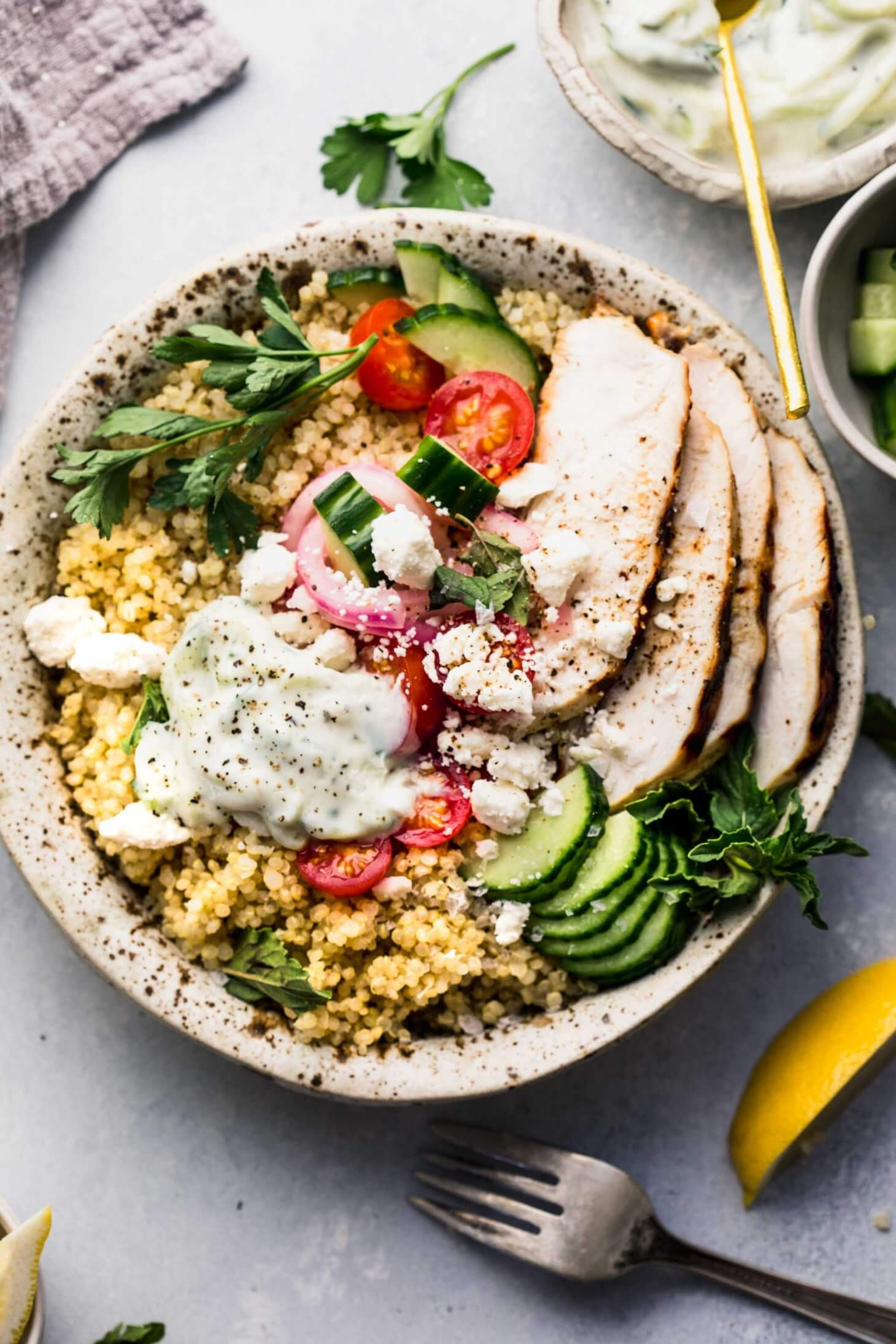Overhead shot of quinoa gyro bowl topped with cucumbers, tomatoes, next to bowl of tzatziki sauce.