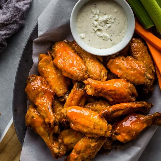 Platter of air fryer chicken wings with buffalo sauce and blue cheese.