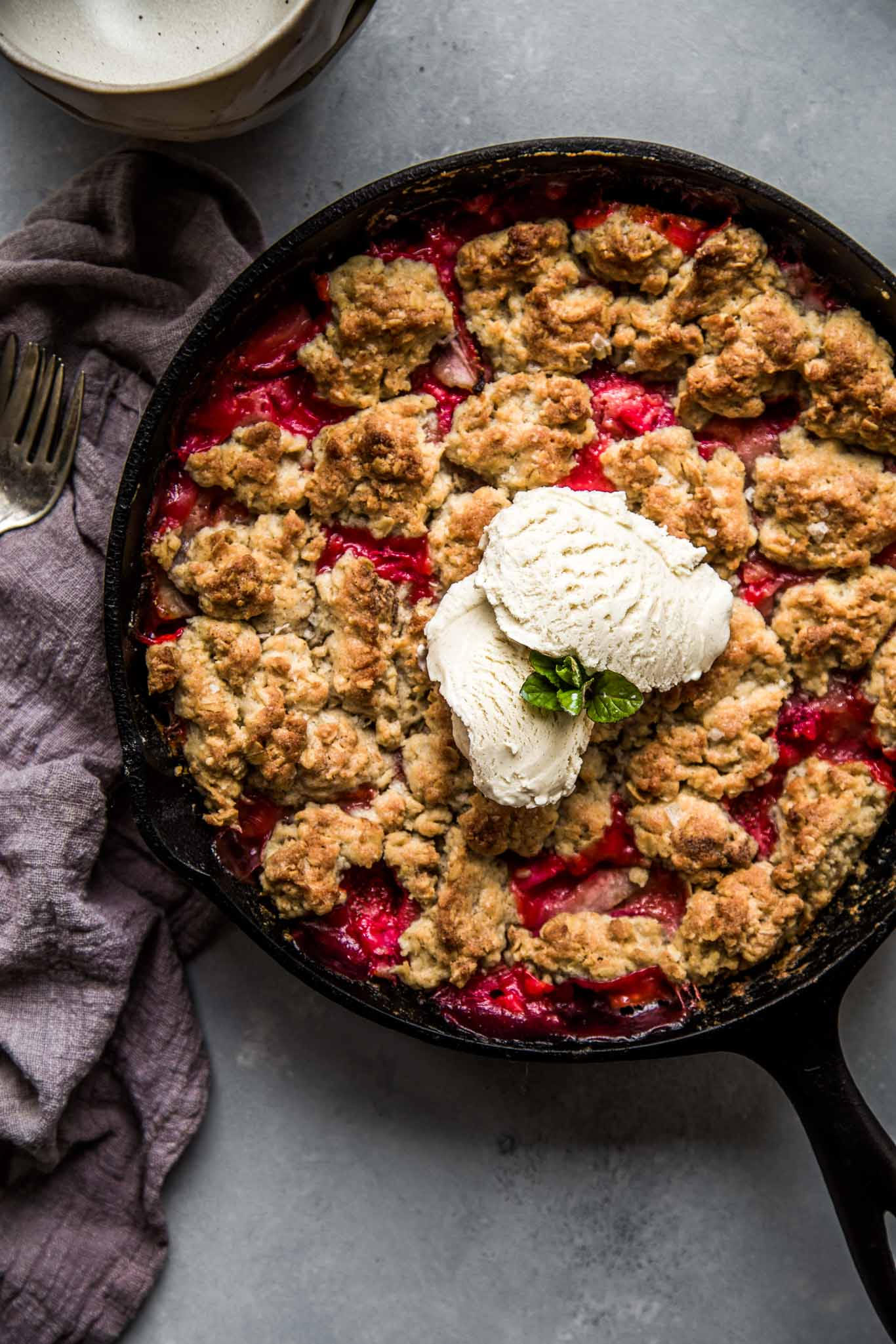Strawberry Rhubarb Skillet Cobbler topped in cast iron skillet topped with vanilla ice cream.