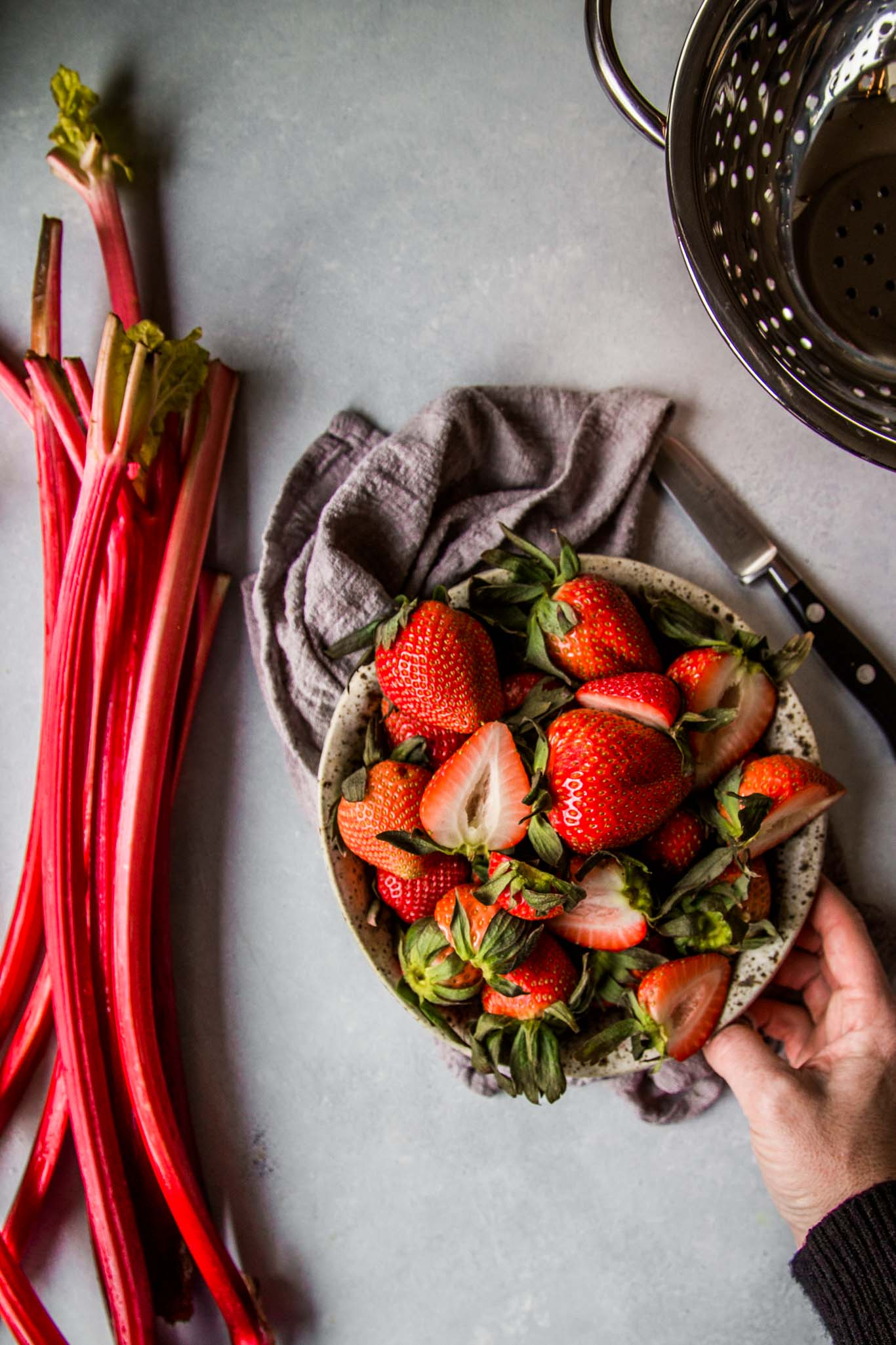 Hand reaching for bowl of strawberries next to rhubarb