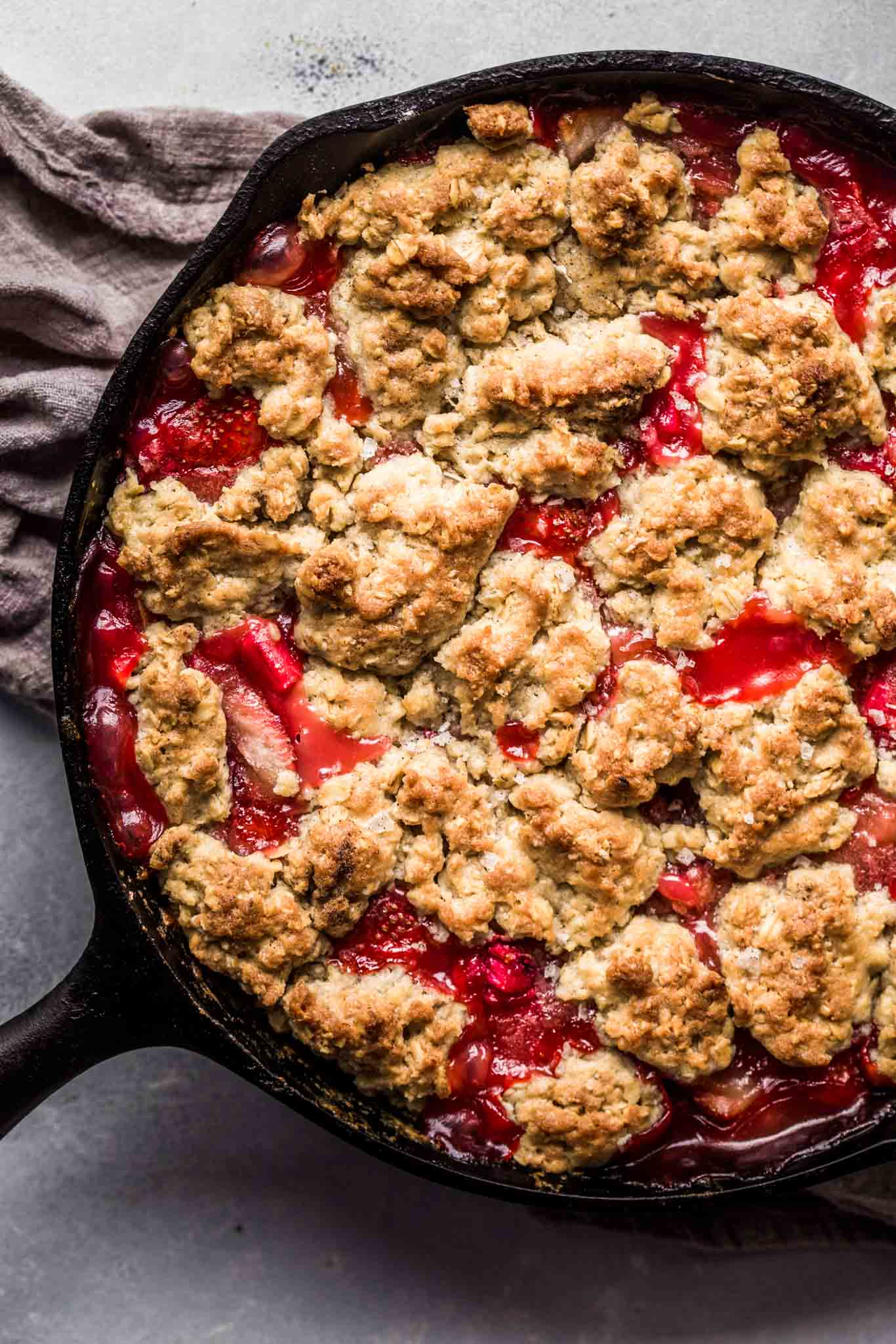 Cast iron strawberry rhubarb cobbler straight out of oven in cast iron skillet