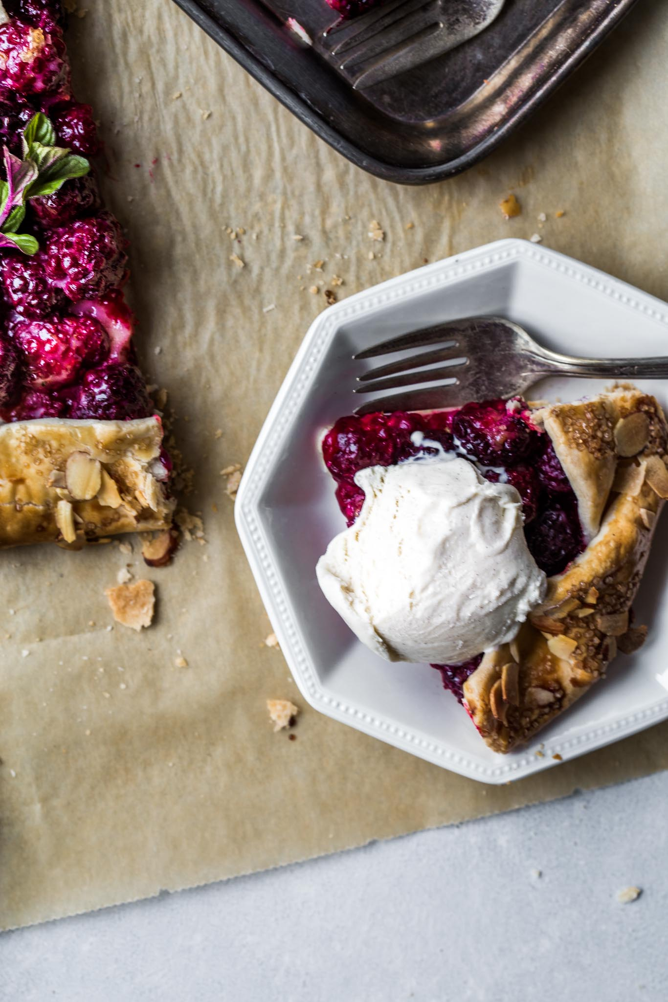 Piece of blackberry galette with scoop of ice cream.