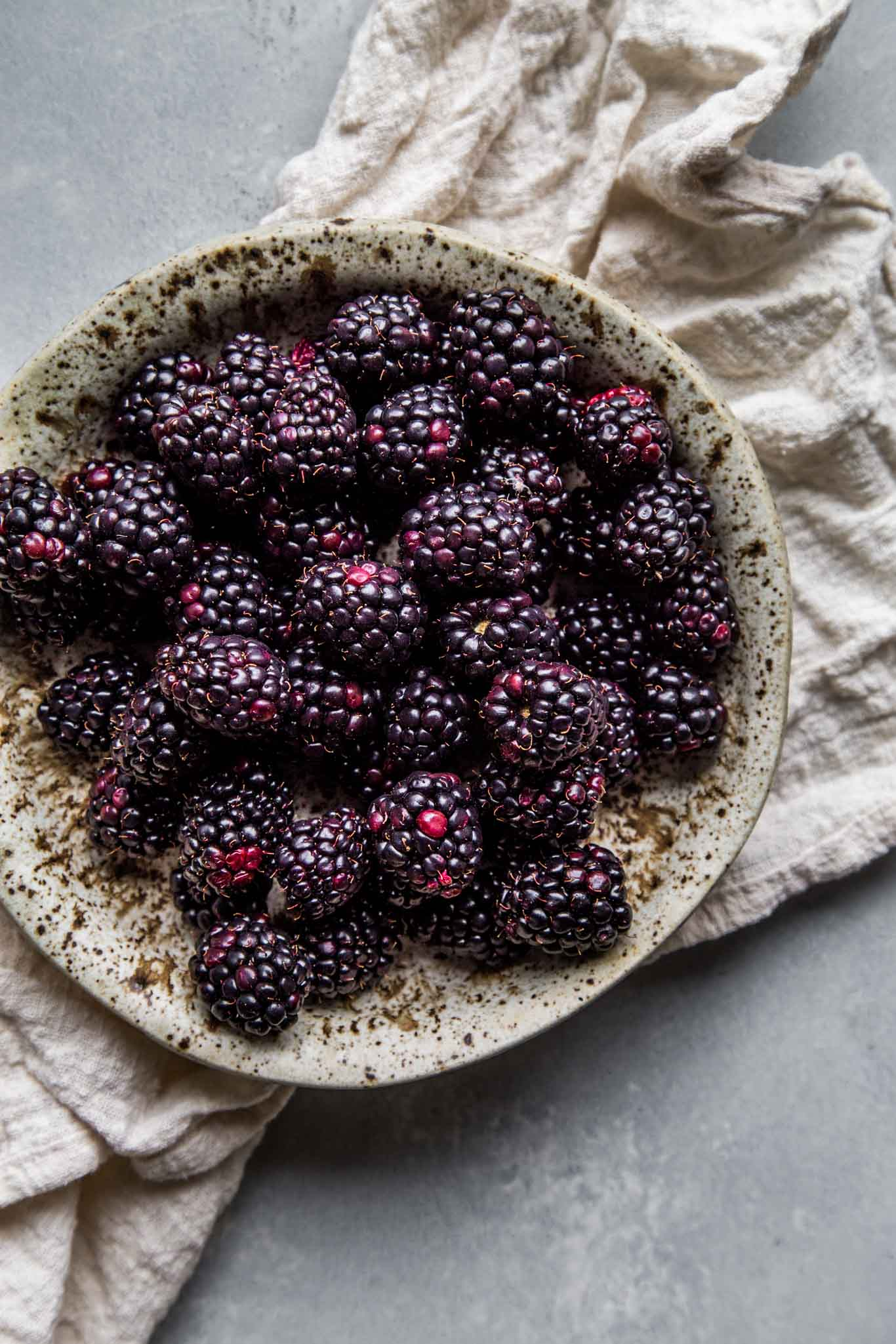 Blackberries in speckled bowl.