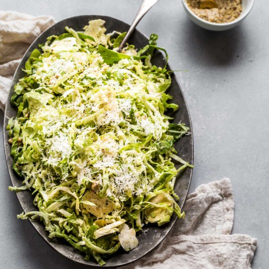 Platter of shaved brussels sprouts salad next to mustard.