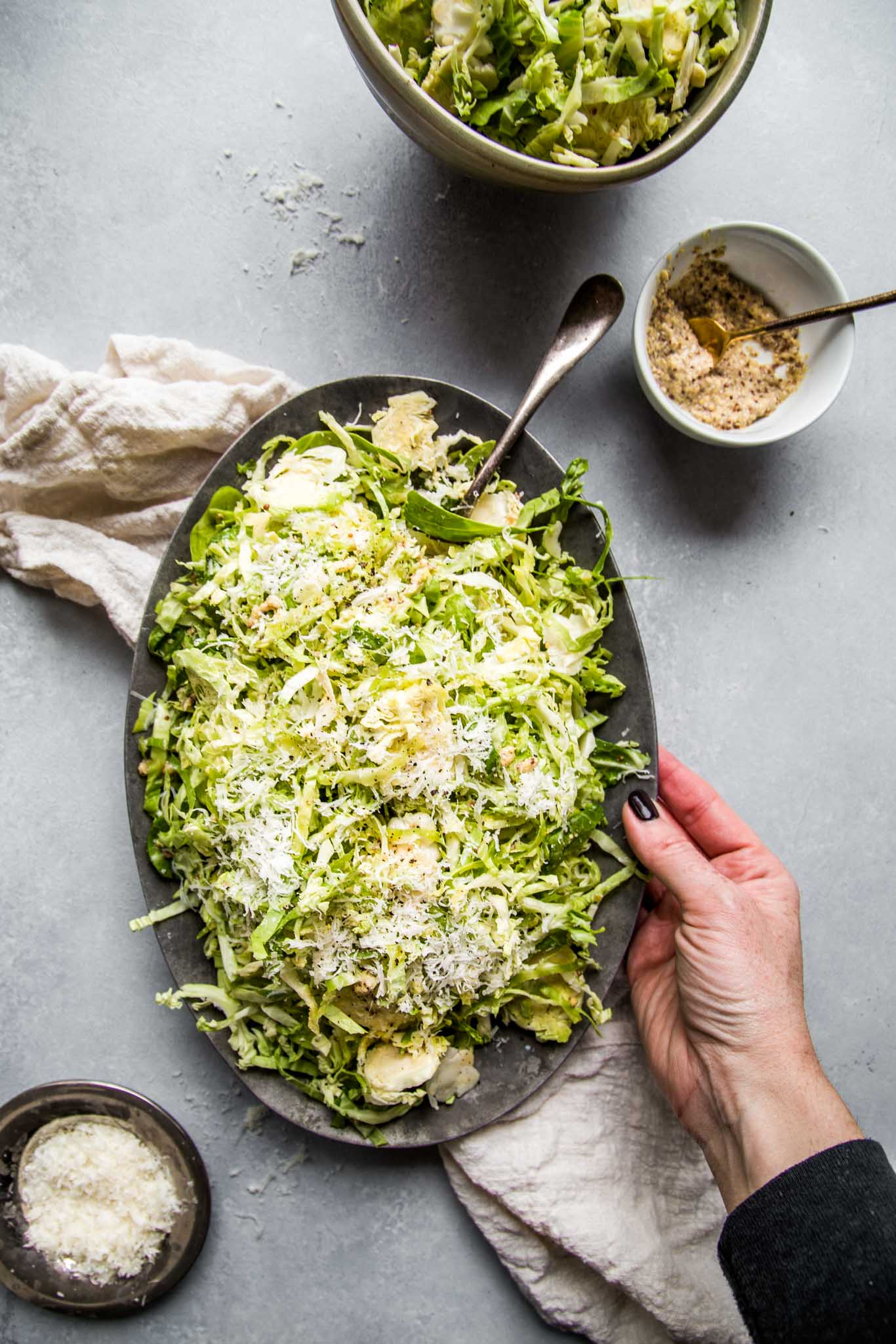 Hand reaching for plate of shaved brussels sprouts salad