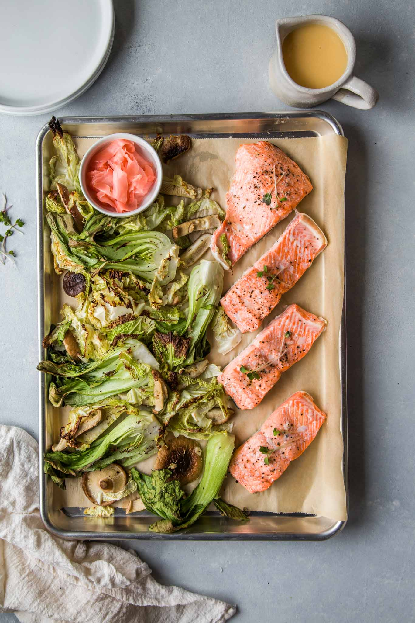 Sheet Pan Salmon out of oven next to roasted vegetables, ginger butter sauce and pickled ginger