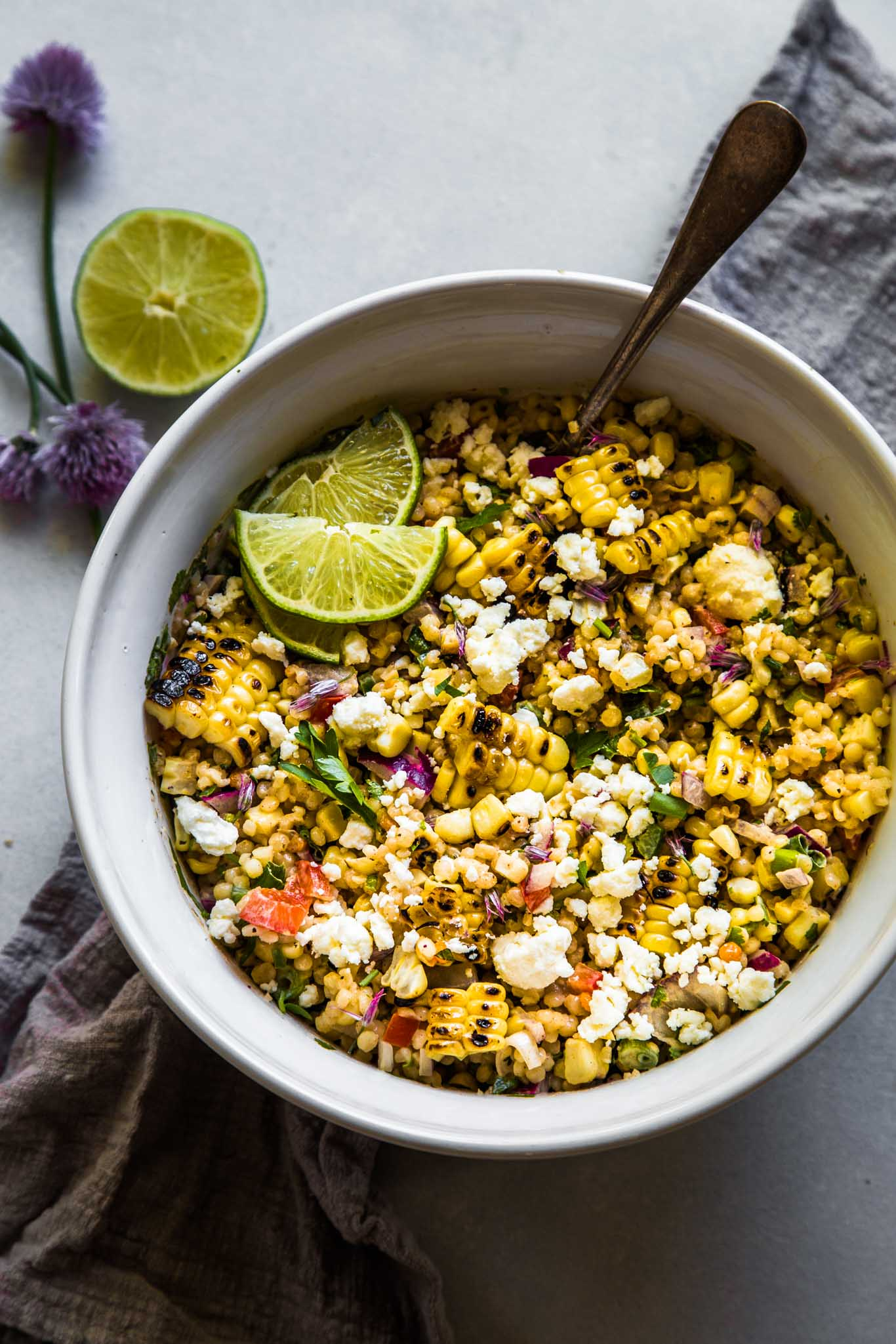 Bowl of Mexican Street Corn Salad next to lime and blooming chives