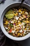 Mexican Street Corn Salad in bowl with wedges of lime.