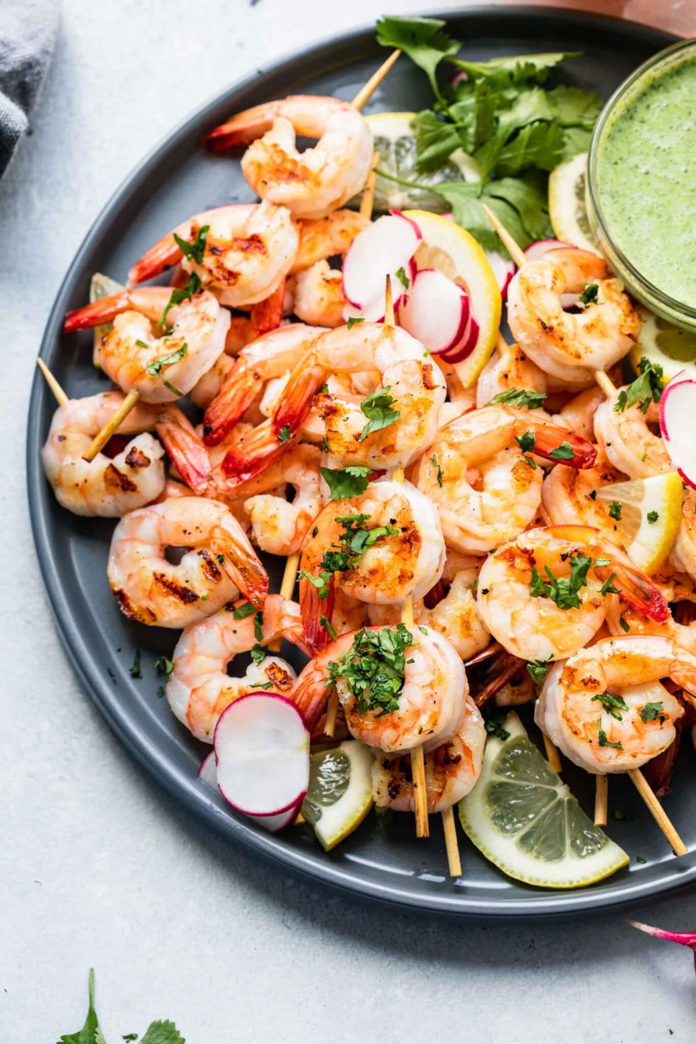 Cooked shrimp skewers arranged on a grey plate with bowl of creamy green sauce.