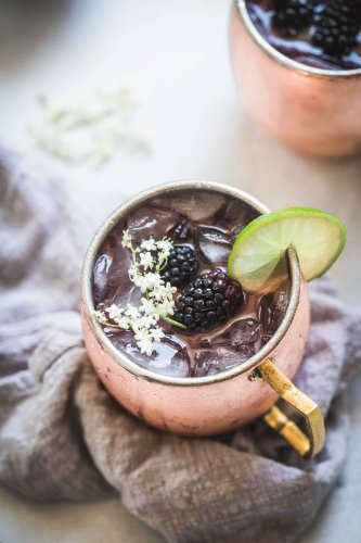 Close up of blackberry moscow mule topped with elderflowers
