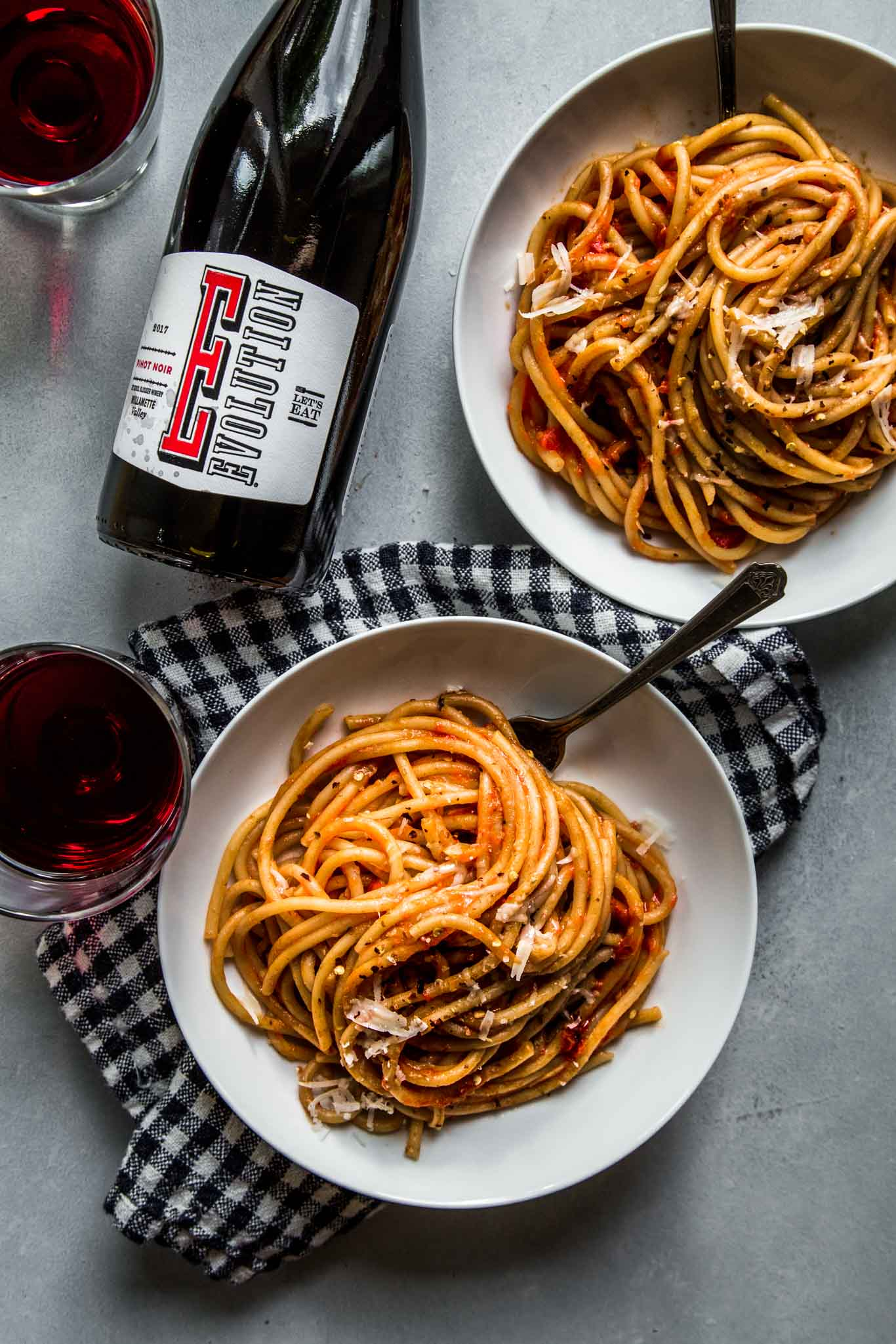 Two plates of pasta with roasted tomato sauce next to wine.