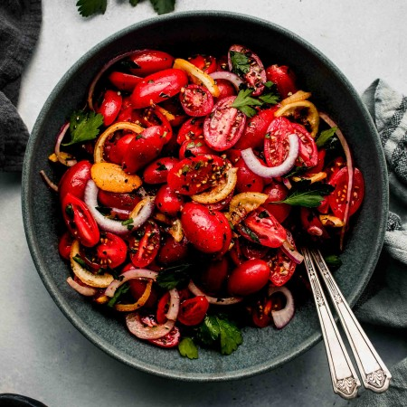 Overhead shot of cherry tomato salad in grey bowl.
