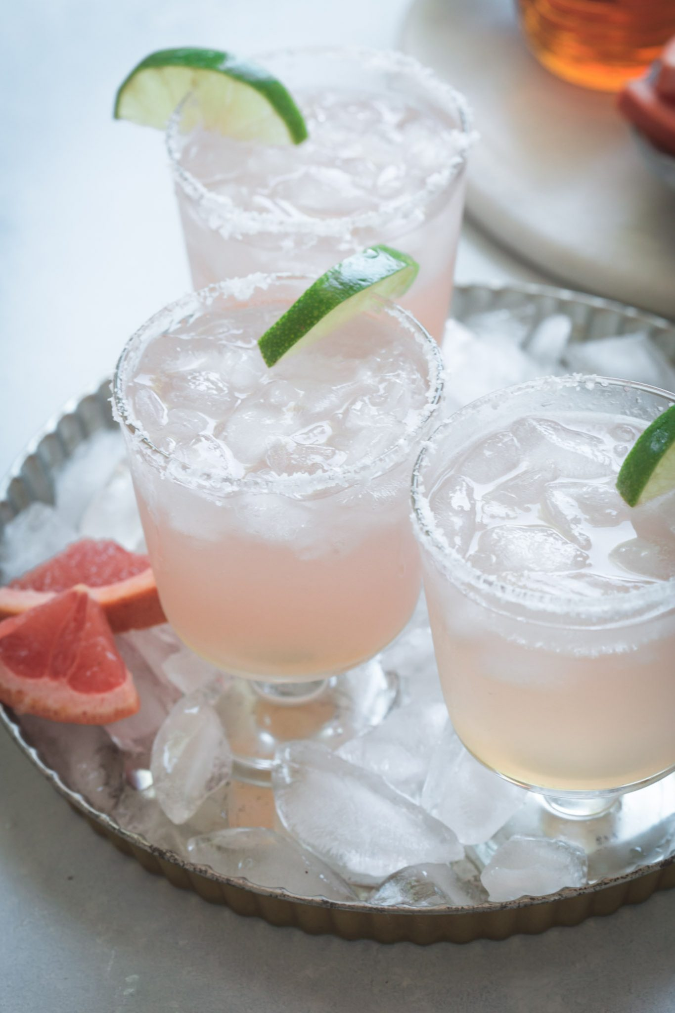 Three paloma cocktails on a serving tray with ice.