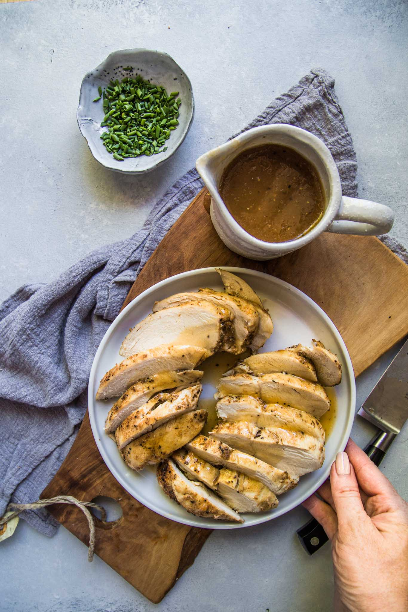Overhead shot of instant pot cooked chicken breasts carved up next to gravy boat.