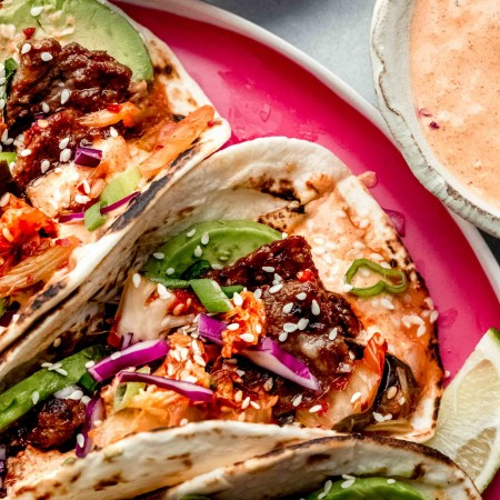Korean tacos arranged on bright pink plate next to small bowls of kimchi and aioli.