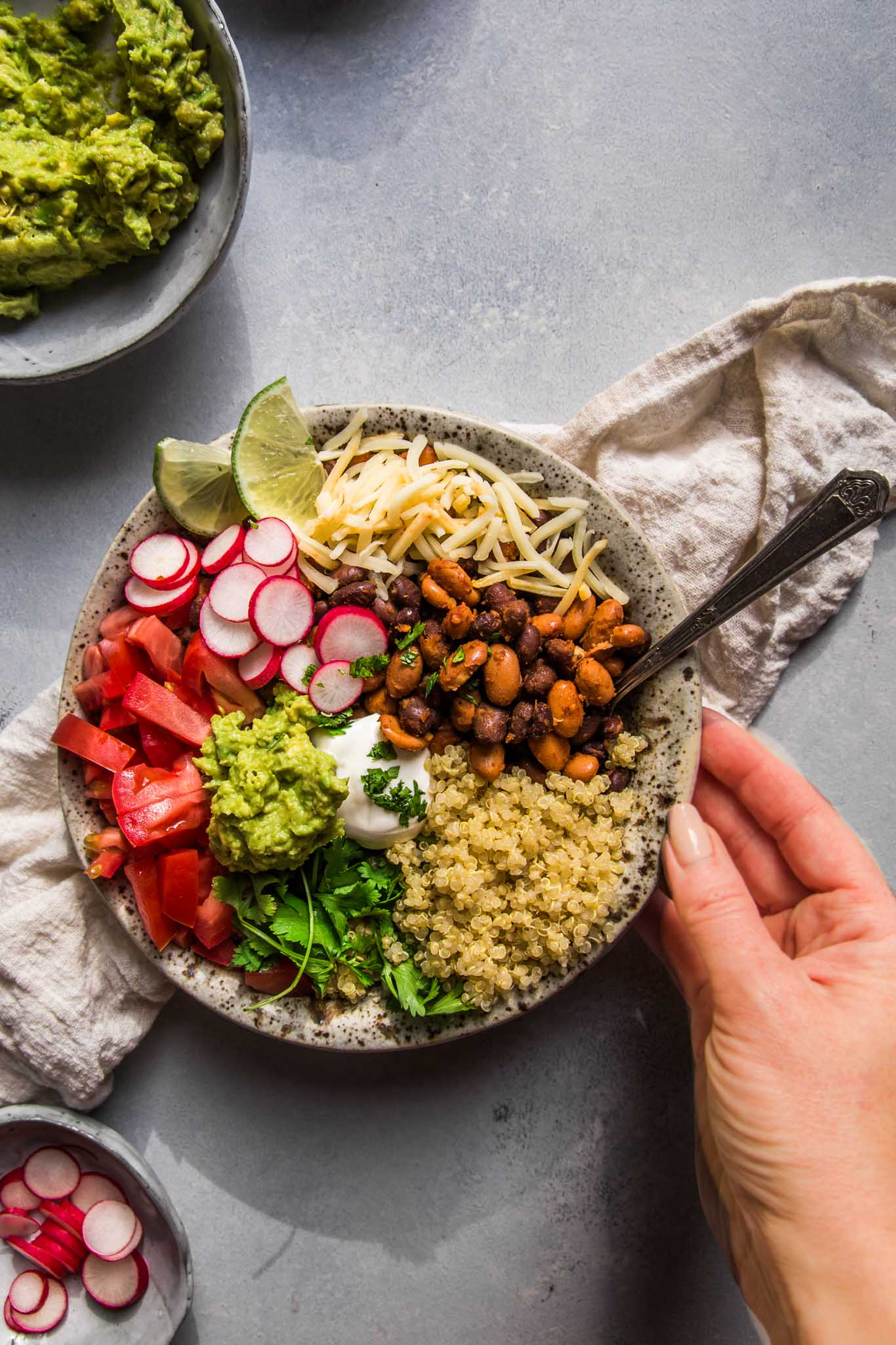 Hand reaching for quinoa taco bowl.