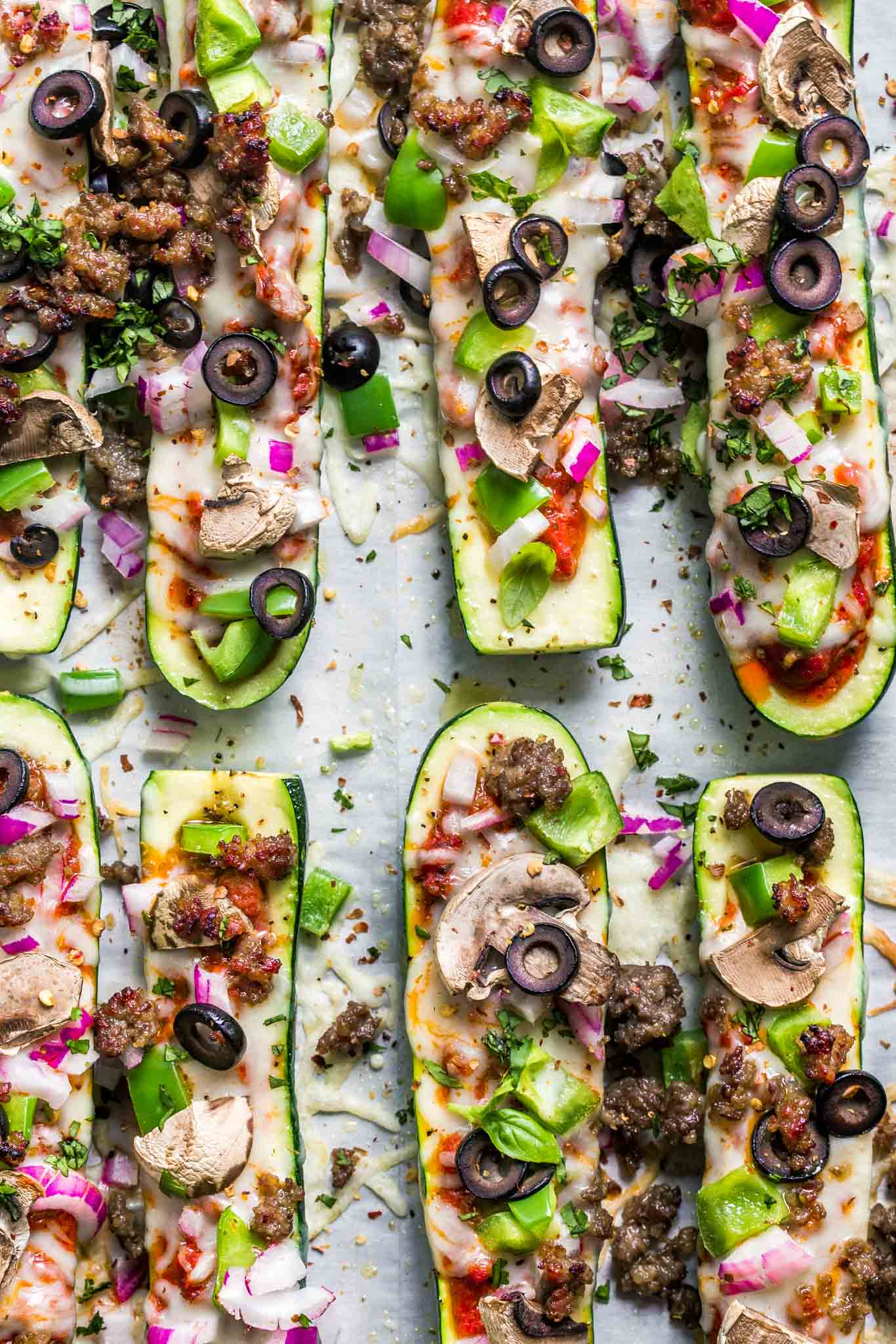 Overhead shot of zucchini pizza boats with supreme toppings.