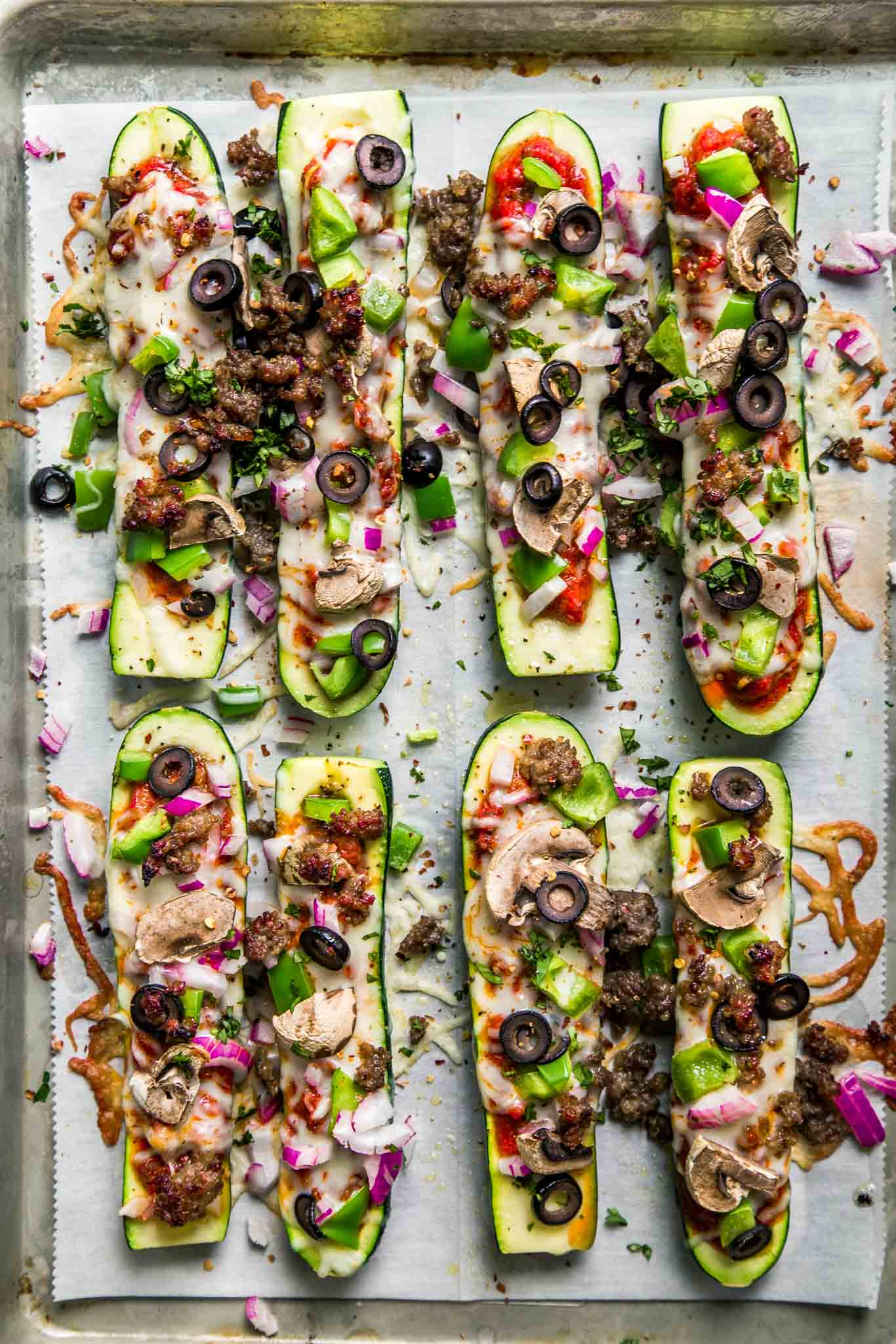 Overhead shot of zucchini pizza boats on baking sheet.