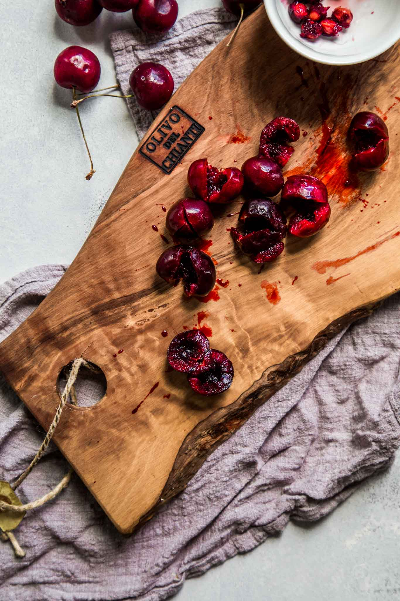 Cherries on a cutting board being pitted.
