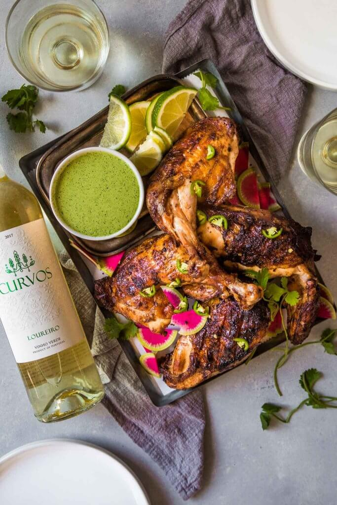 Bottle of vinho verde next to peruvian chicken.