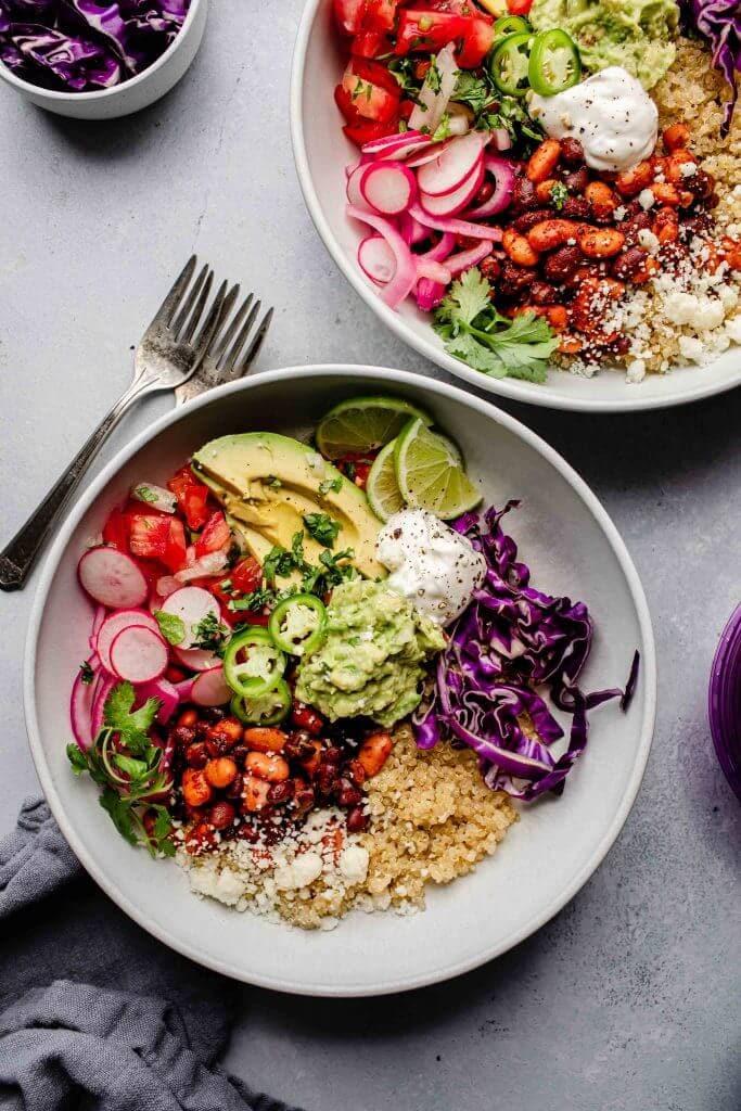 Two quinoa burrito bowls arranged on counter.