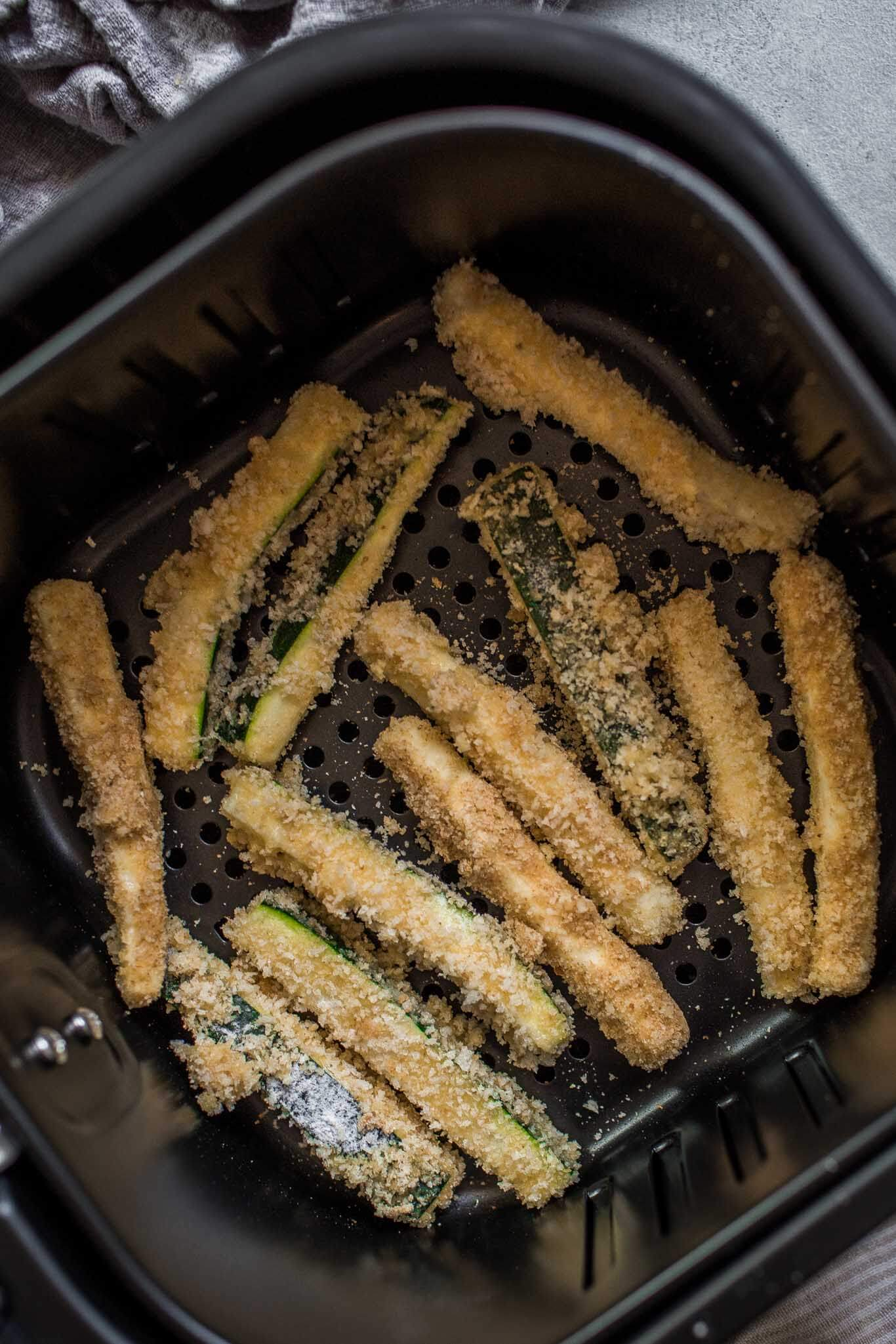 Zucchini fries in air fryer basket.