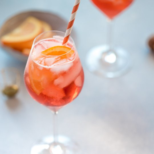 Aperol spritz cocktail in wine glass with orange and white straw