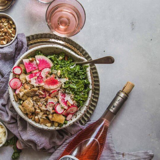 Overhead shot of Kale Caesar Salad with bottle and glasses of rosé wine.