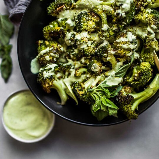 Overhead shot of roasted broccoli next to bowl of basil tahini sauce.