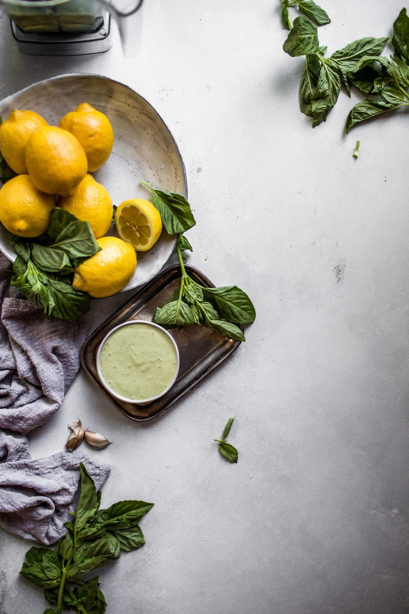 Bowl of creamy green tahini sauce next to bowl of lemons and basil.