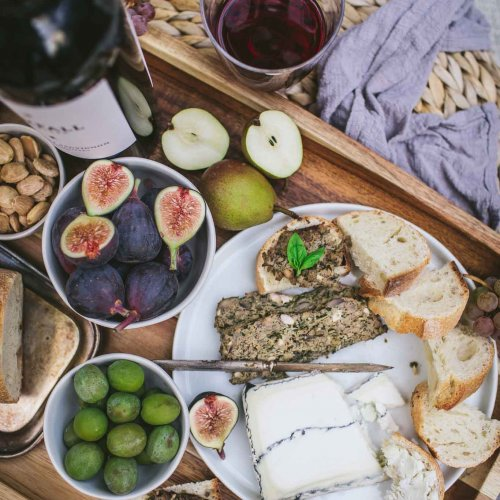 Overhead shot of mushroom pate on platter with olives, figs and cheese.
