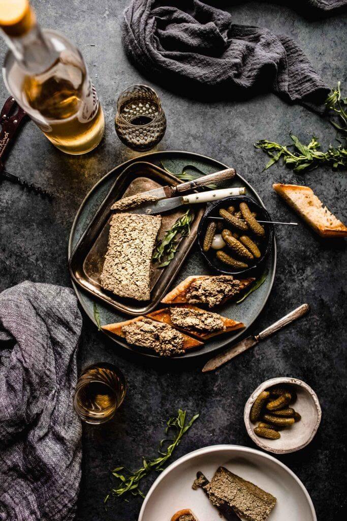 Mushroom pate on dark grey plate next to crostini and bowl of gherkins.