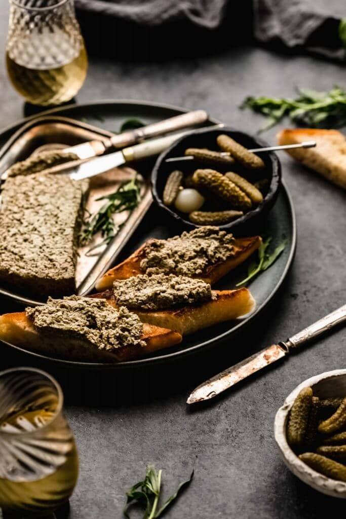 Side view of Mushroom pate on dark grey plate next to crostini and bowl of gherkins.