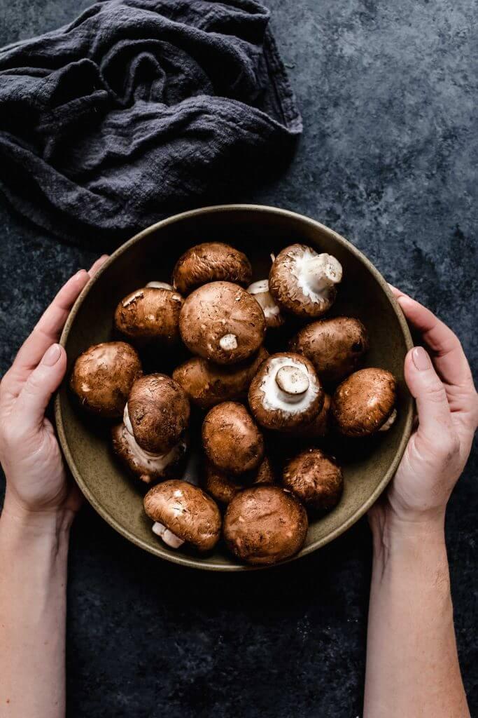 Hands holding bowl of cremini mushrooms.
