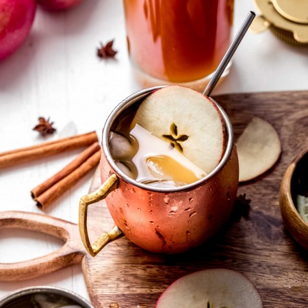 Apple cider moscow mule on serving tray garnished with apple slices and cinnamon stick.