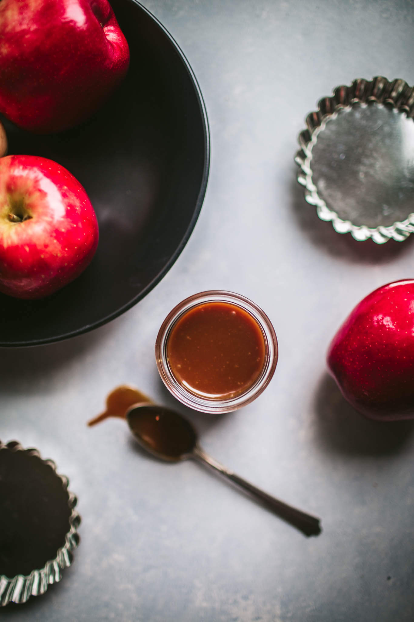 Salted caramel sauce next to bowl of apples.