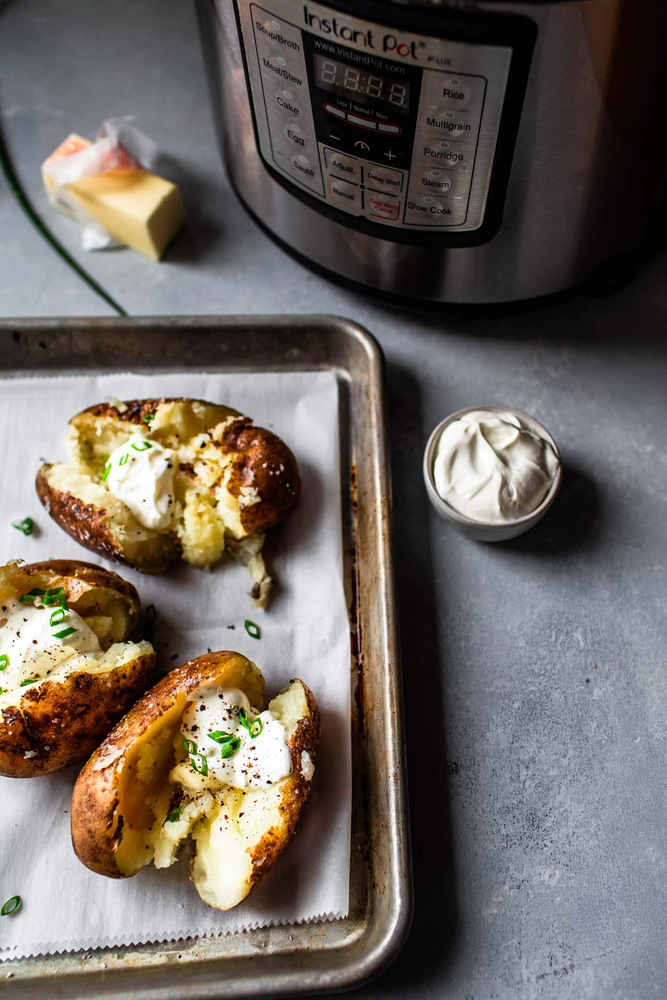 Baked potatoes on baking sheet next to instant pot.