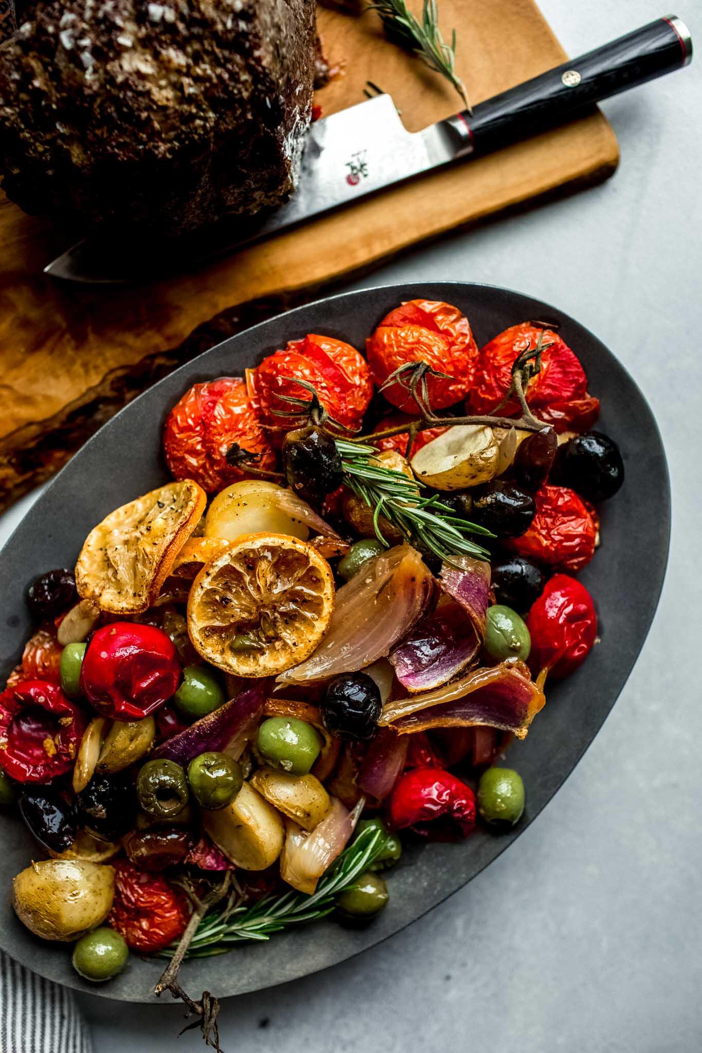 Cooked vegetables and olives on serving platter.