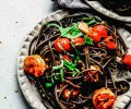 Overhead shot of plate of squid ink pasta topped with shrimp & tomatoes.