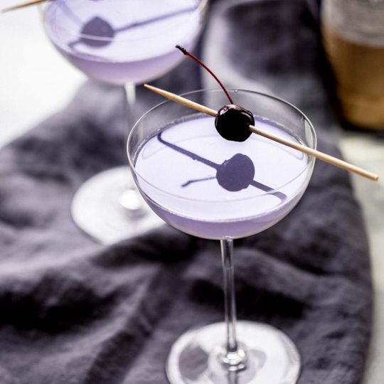 Two aviation cocktails garnished with cherries next to alcohol bottles.
