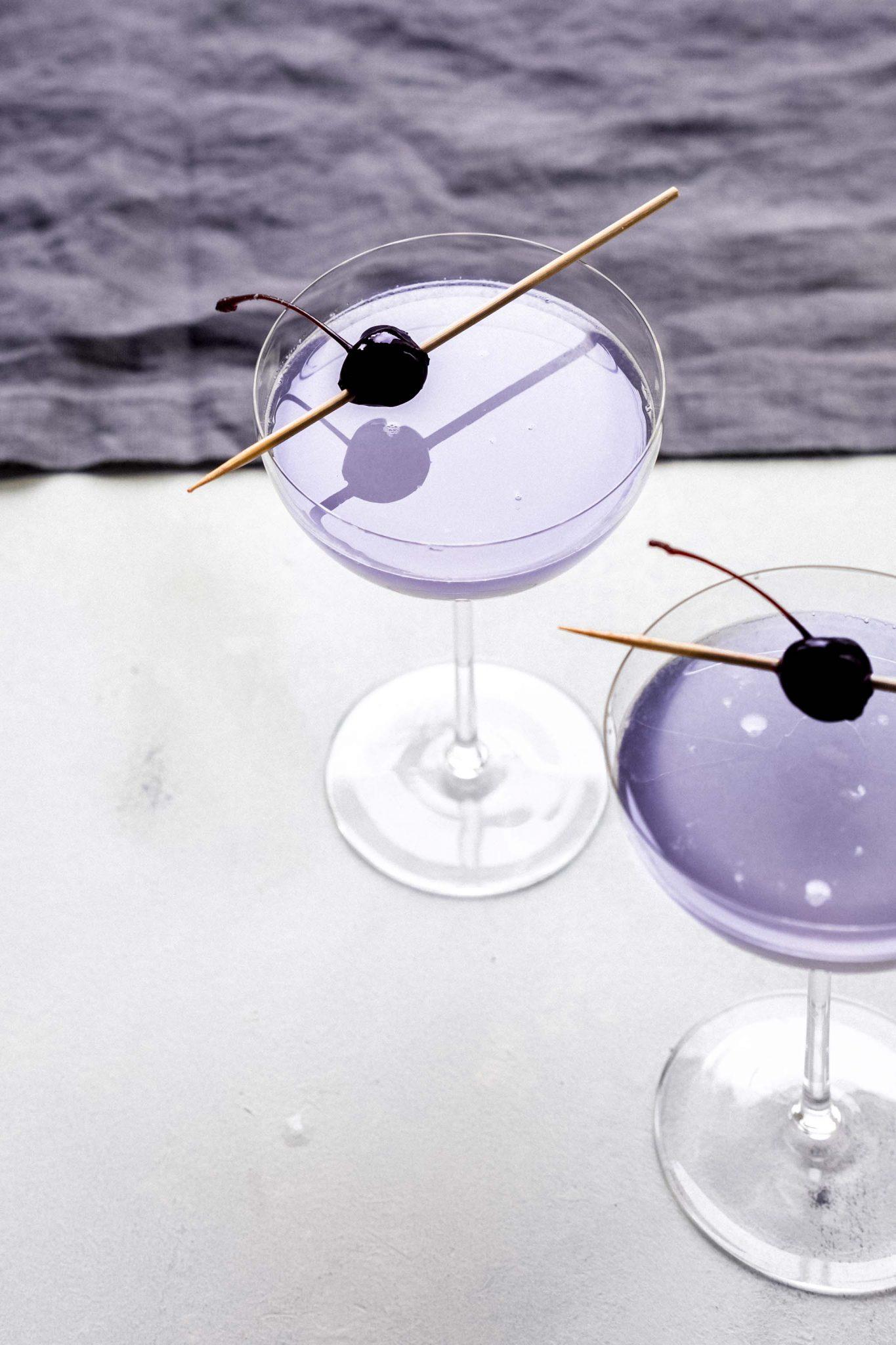 Twee Aviation Cocktails van de zijkant gefotografeerd.
