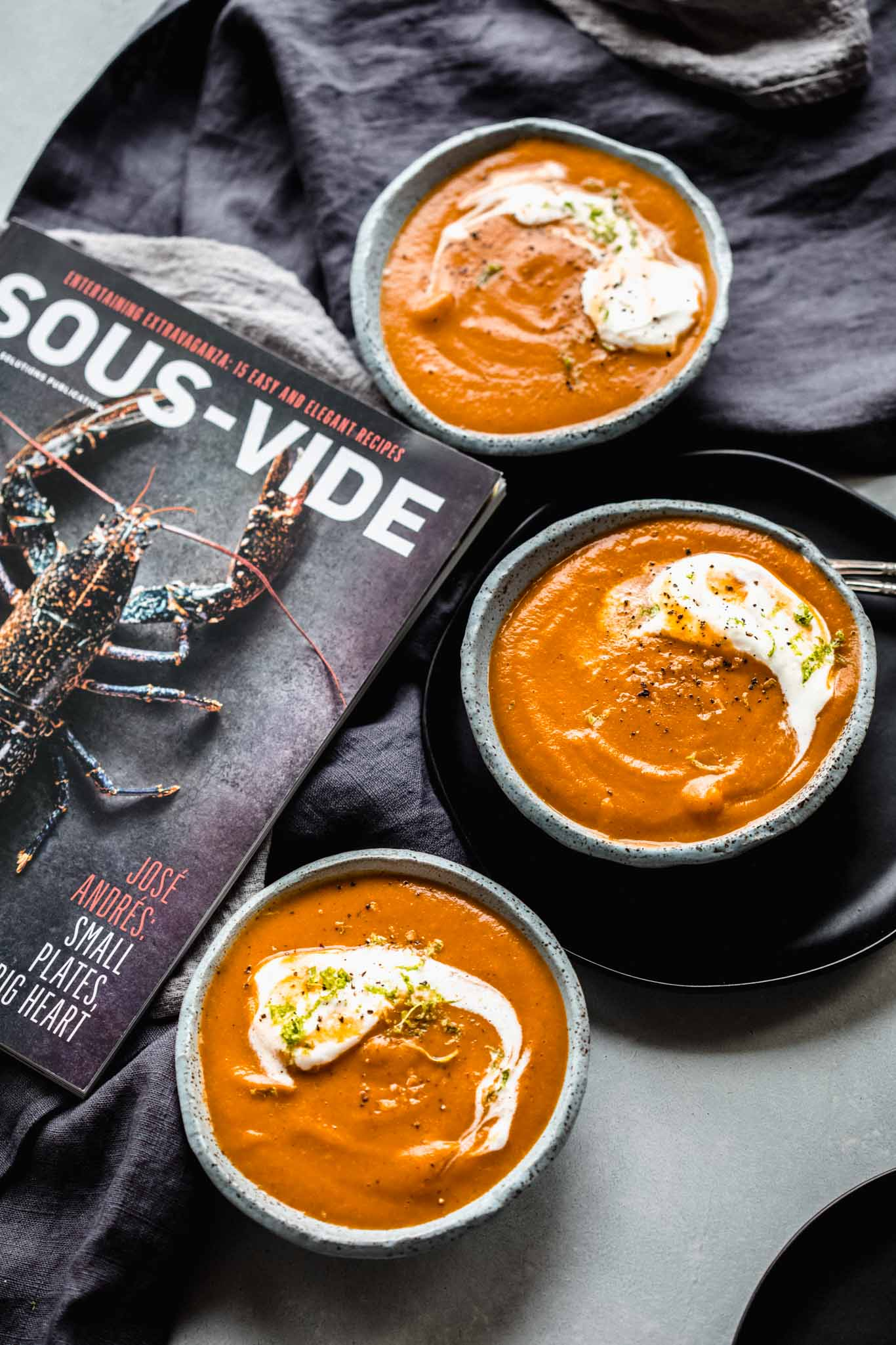 Bowls of carrot ginger soup next to sous vide magazine.