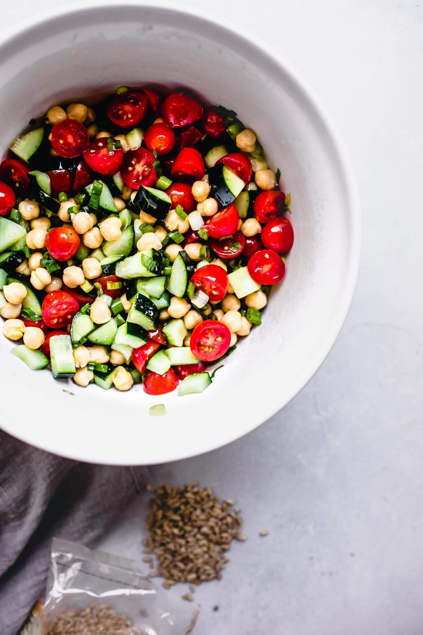 Tomatoes, chickpeas and cucumber in white mixing bowl.