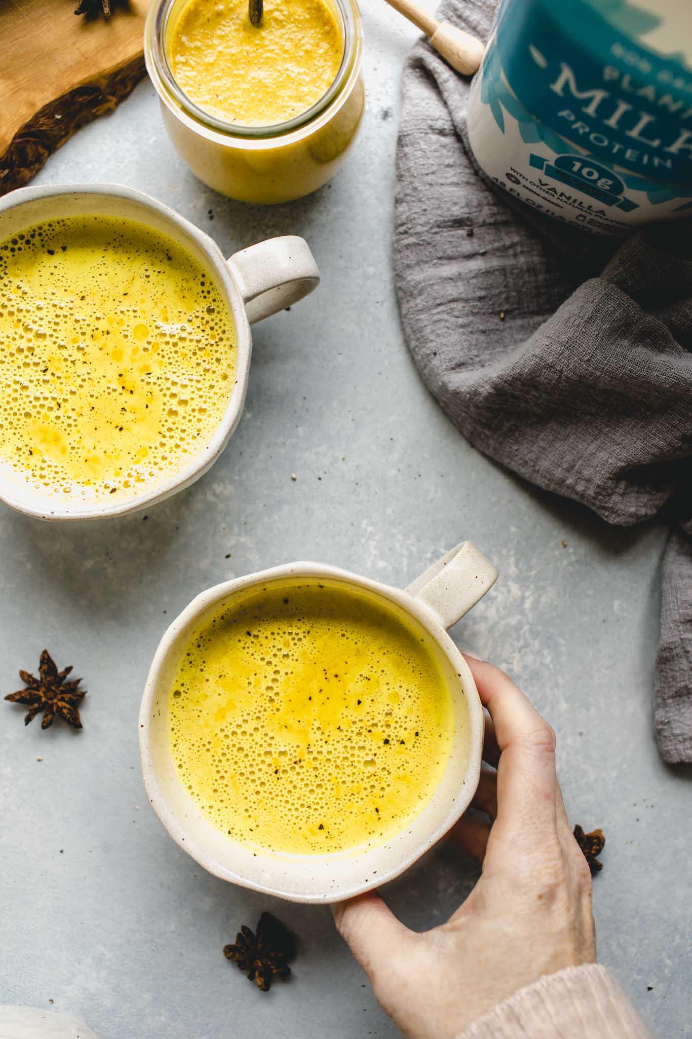 Hand holding mug of Golden Milk Latte.