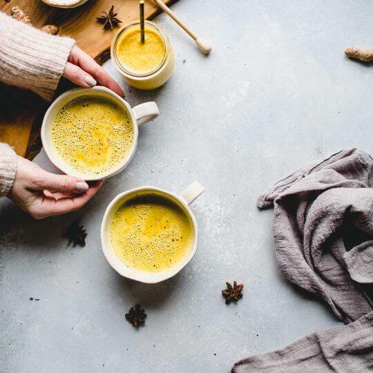 Hand holding cup of golden milk latte.
