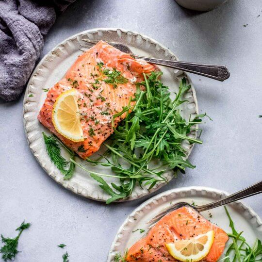 Two plates of cooked salmon.