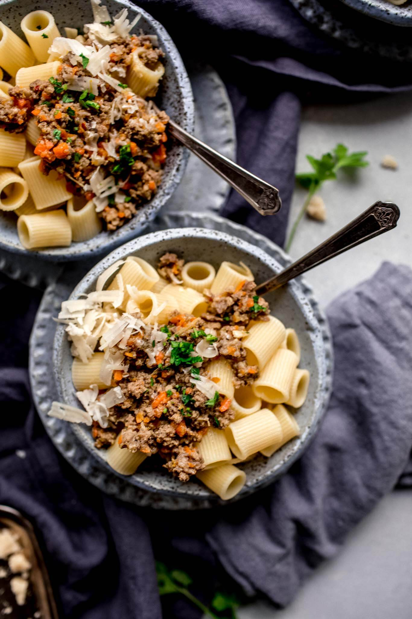 Two bowls of pasta with white bolognese.