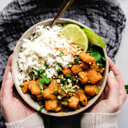Two hands holding bowl of butternut squash curry with rice.